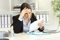 Worried executive reading a letter at office. Worried executive reading bad news in a letter at office Stock Image