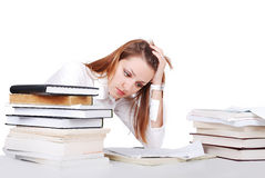 Worried expression on female students face. Young student with many books on the desk Stock Photos