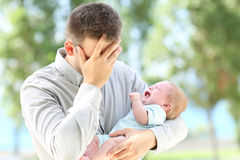Worried father and baby crying. Outdoors stock photography