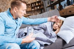 Worried father feeling the forehead of his ill son. Extremely worried. Pleasant young men sitting on the sofa next to his diseased son and feeling his forehead Stock Image