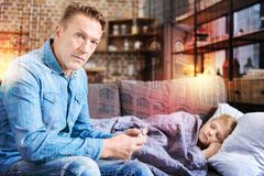 Worried father holding a thermometer while his son resting on the sofa. Serious parent. Attentive supporting parent looking serious while holding a thermometer stock photos