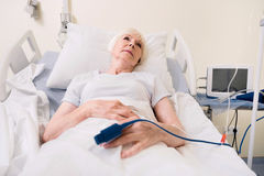 Worried feeble woman hoping for quick recovery. Improving condition. Ailing bright aged lady resting on a bed while recovering and restoring her strength after royalty free stock image
