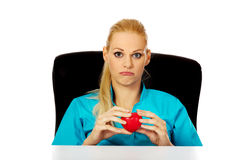 Worried female doctor or nurse sitting behind the desk and holding heart model Stock Photography