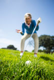 Worried female golfer looking at golf ball Stock Photos
