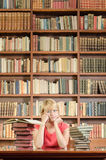 Worried female student with elbows on library table Royalty Free Stock Image