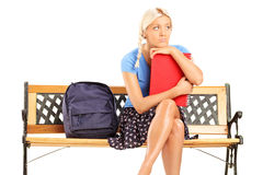 Worried female student sitting on a bench Royalty Free Stock Photo