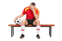 Worried football player sitting on a bench Royalty Free Stock Image