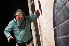 Worried Gang Member Spray Painting. Scared disguised criminal defacing a wall outdoors Stock Photos