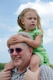 Worried girl on grandpas shoulders Royalty Free Stock Photo