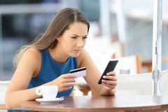 Worried girl having problems paying on line. Single worried girl having problems paying on line with a credit card and a phone in a coffee shop terrace Royalty Free Stock Image