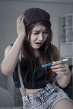 Worried girl holding pregnancy test Royalty Free Stock Photography