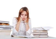 Worried girl between lot of books Stock Photo