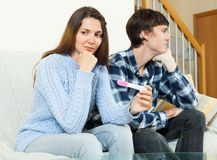 Worried girl with pregnancy test with unhappy man Stock Photos