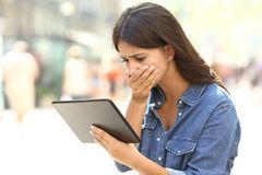 Worried girl reading online news in a tablet. In the street Royalty Free Stock Images