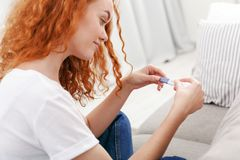 Worried girl reading the results of her pregnancy test. Worried redhead girl checking her recent pregnancy test, sitting on beige couch at home Stock Images