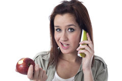 Worried girl speaking on the phone and eating an apple Stock Photo
