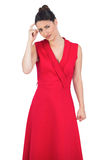Worried glamorous model in red dress posing Royalty Free Stock Photos