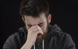 Worried Goatee Young Man with Hand on Face. Close up Worried Handsome Goatee Young Man Wearing in Gray Jacket with Hand on Face. Isolated on Black Background Stock Photo