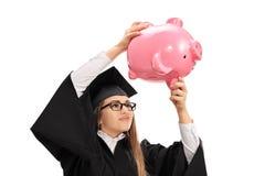 Worried graduate student shaking a piggybank Stock Image