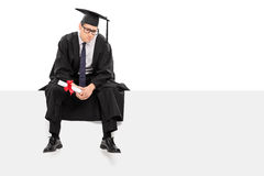 Worried graduate student sitting on a signboard Stock Photo