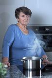 Worried grandma standing in the kitchen. Picture of worried grandma standing in the kitchen royalty free stock images