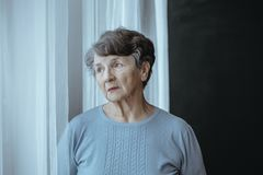 Worried grandmother with alzheimer`s disease. Isolated looking through window in nursing house royalty free stock photography