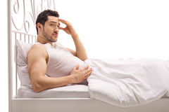 Worried guy lying in bed Stock Image