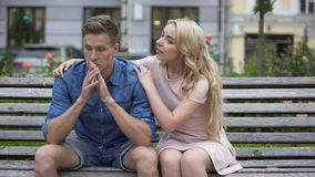 Worried guy sitting on bench, girlfriend calming him down, problems, support. Stock footage stock footage