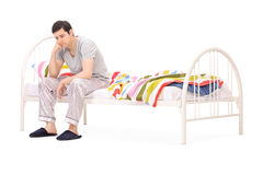 Worried guy sitting on a wooden bed Royalty Free Stock Image