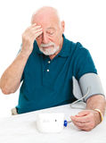 Worried About High Blood Pressure. Worried senior man monitors his blood pressure at home royalty free stock image