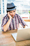 Worried hipster businessman using laptop Royalty Free Stock Photography