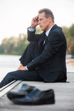 Worried about his business. Side view of thoughtful businessman holding hand on chin and looking away while sitting barefoot at the quayside and with shoes Stock Images
