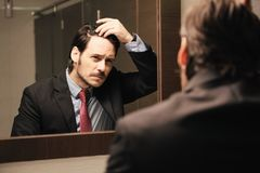 Worried Hispanic Business Man Looking At Hairline In Office Restrooms. Business man in office bathroom. Stressed manager using restrooms, washroom and lavatories stock photography