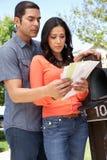 Worried Hispanic Couple Checking Mailbox Royalty Free Stock Photography