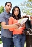 Worried Hispanic Couple Checking Mailbox Stock Photography
