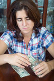 Worried  hispanic woman counting her savings at home Stock Photos