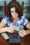 Worried  hispanic woman counting her savings at home Royalty Free Stock Photography