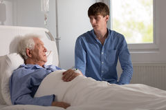 Worried ill patient. Talking with his grandson Stock Photos