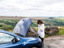 Worried lady at car breakdown. Mature lady looking at car engine after car breakdown in remote countryside Royalty Free Stock Photo