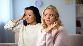 Worried lady telling her best friend shocked news, private conversation at home. Stock photo stock image