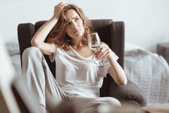 Worried lady thinking about her problems while drinking wine. What should I do. Confused stressed woman trying to solve her problem and drinking white wine at Royalty Free Stock Image