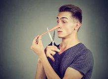 Worried liar man wants to cut his long nose. Isolated on gray wall background Royalty Free Stock Photo