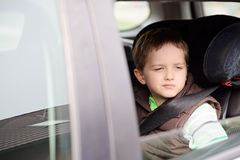 Worried little boy in car safety seat. Royalty Free Stock Photography