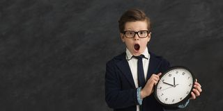 Excited little boy with clock at gray background. Worried little boy with clock at gray studio background, copy space. Being late, time is the most precious stock photography