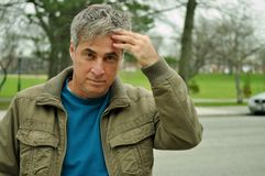 Worried look. This picture represents a worried look mature man with one hand on his forehead Stock Photo