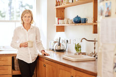 Worried looking senior woman standing in her kitchen Stock Photography