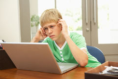 Worried Looking Teenage Boy Using Laptop At Home Stock Photos