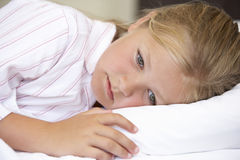 Worried Looking Young Girl In Bed Stock Photography