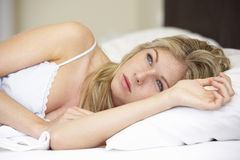 Worried Looking Young Woman On Bed Stock Images