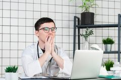 Worried male doctor using a laptop in his practice stock images